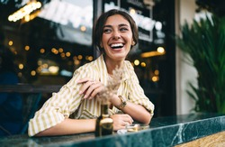 Cheerful young ethnic female in trendy outfit laughing and looking away while chilling at marble counter on cozy cafe terrace
