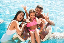 Cheerful young family having fun together at the swimming pool outdoors in summer, swimming with inflatable ring donut, waving hands