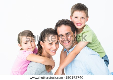 Cheerful young family looking at camera together on white background