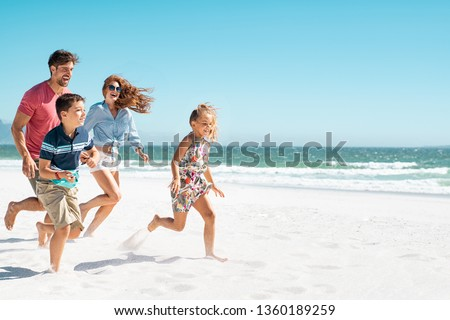 Cheerful young family running on the beach with copy space. Happy mother and smiling father with two children, son and daughter, having fun during summer holiday. Playful casual family enjoying.