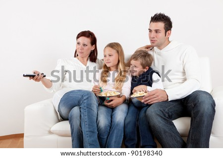 Cheerful young family watching TV together at home