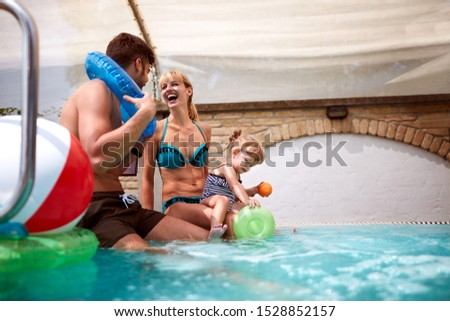 Cheerful young family with kid enjoying on pool