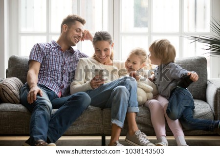Cheerful young family with kids laughing watching funny video on smartphone sitting on couch together, parents with children enjoying playing games or entertaining using mobile apps on phone at home #1038143503