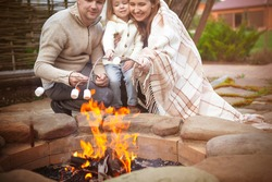 Cheerful young family with little daughter toasting marshmallow over bonfire while enjoying time together in patio of country house