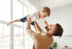 Cheerful young father holding up excited little boy while spending time together and having fun in light room at home