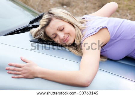 Cheerful young female driver hugging her new car