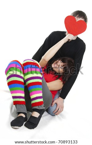 cheerful young female hiding boyfriend's face by red heart