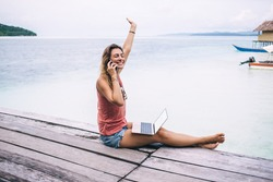 Cheerful young female in casual summer clothes raising hand and smiling brightly with closed eyes while using modern smartphone and digital laptop on vacation on pier in nature