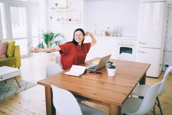 Cheerful young female in eyeglasses stretching out with raised hands and relaxing after work on laptop at desk in modern light living room looking away