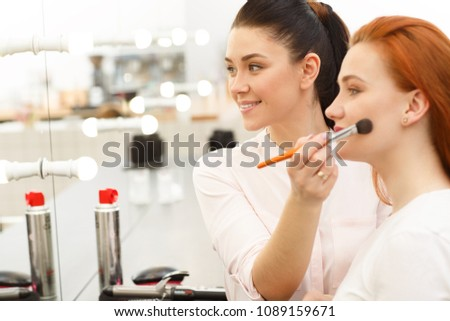 Cheerful young female makeup artist smiling enjoying working with a beautiful young red haired female model, applying makeup on her face using powder brush copy space