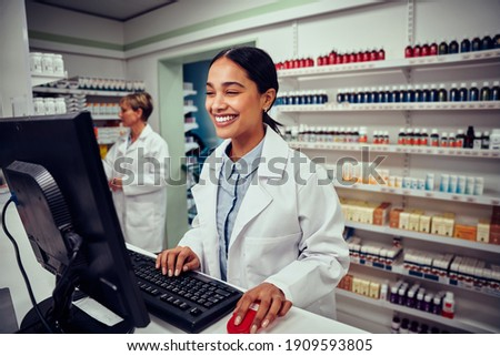 Cheerful young female pharmacist wearing labcoat working on computer in drugstore