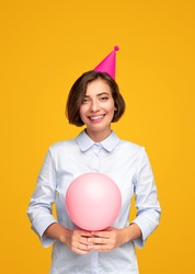 Cheerful young female with pink balloon and party cap smiling and looking at camera while celebrating birthday against yellow background