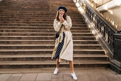Cheerful young girl in French beret, beige trench coat, polka dot skirt and white sneakers posing full length, laughing and looking into camera against sunlit stairs background