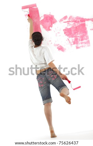 Cheerful young girl painting a wall with roller