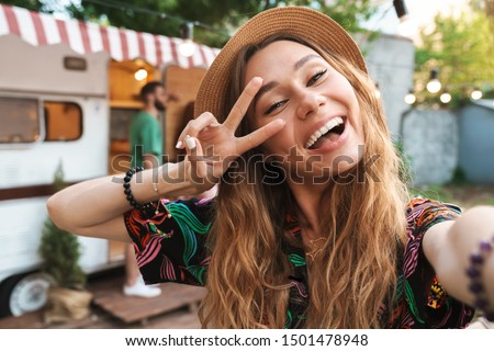 Cheerful young girl taking a selfie while standing at the campsite with a trailer on a background