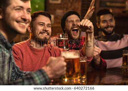 Cheerful young handsome male friends having fun at the beer pub celebrating victory of their favorite team watching game on TV happiness people leisure entertainment bar restaurant friendship
