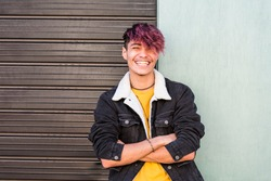 Cheerful young happy boy teenager hispanic race smile and laugh in front of the camera in posed portrait - two colors background urban style - youth teenager enjoy - violet diversity hair