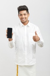 Cheerful Young Indian man showing smart phone in traditional dress