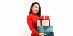 Cheerful young lady holding gift boxes in hands and looking at camera with toothy smiles while preparing for Lunar New Year celebration, isolated on white background