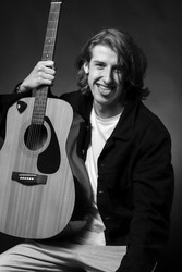 Cheerful young male guitarist posing with his guitar in the studio on a black background.