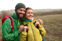 Cheerful young man and woman in colorful outerwear with backpacks laughing and looking away while standing together in autumn field during hiking