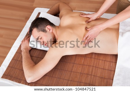 Cheerful young man getting shoulder massage at spa