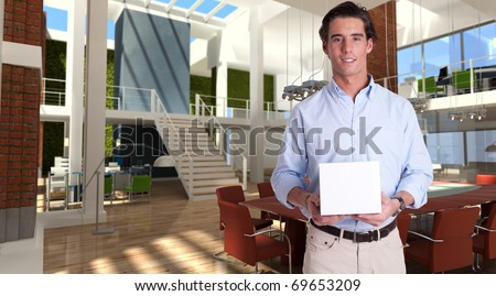 Cheerful young man holding a white box in a modern luxurious office