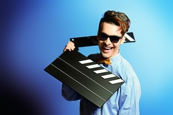 Cheerful young man holding clapper board. Cinema industry. Different occupations.