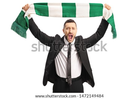 Cheerful young man in a suit cheering with a scarf isolated on white background #1472149484