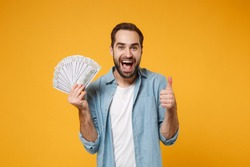 Cheerful young man in blue shirt posing isolated on yellow orange background in studio. People lifestyle concept. Mock up copy space. Holding fan of cash money in dollar banknotes, showing thumb up