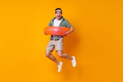Cheerful young man in cap, sneakers, shorts and shirt is having fun and jumping with inflatable circle on orange background