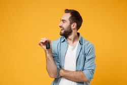 Cheerful young man in casual blue shirt posing isolated on yellow orange background, studio portrait. People emotions lifestyle concept. Mock up copy space. Holding in hand car keys, looking aside