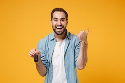 Cheerful young man in casual blue shirt posing isolated on yellow orange background, studio portrait. People lifestyle concept. Mock up copy space. Holding car keys, showing thumb up, pointing aside