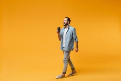 Cheerful young man in casual blue shirt posing isolated on yellow orange background, studio portrait. People sincere emotions lifestyle concept. Mock up copy space. Hold paper cup of coffee or tea