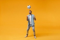 Cheerful young man in casual blue shirt posing isolated on yellow orange wall background, studio portrait. People sincere emotions lifestyle concept. Mock up copy space. Catching soccer ball in air