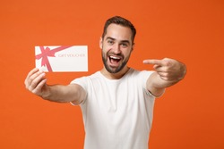 Cheerful young man in casual white t-shirt posing isolated on orange background studio portrait. People sincere emotions lifestyle concept. Mock up copy space. Point index finger on gift certificate