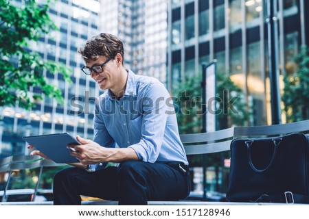 Cheerful young man in formal wear watching funny video on website on modern touch pad device use wireless internet, positive male employee in optical spectacles reading news on digital tablet
