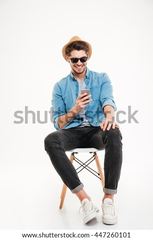 Cheerful young man in hat and sunglasses sitting and using smartphone over white background #447260101