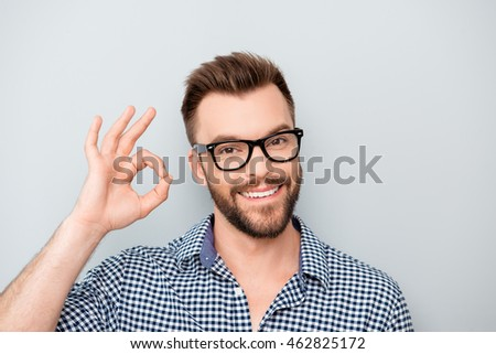 "Cheerful young man in spectacles showing ""OK"" gesture #462825172"