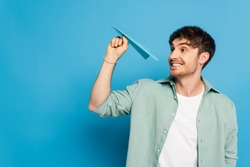 cheerful young man throwing paper plane while looking away on blue