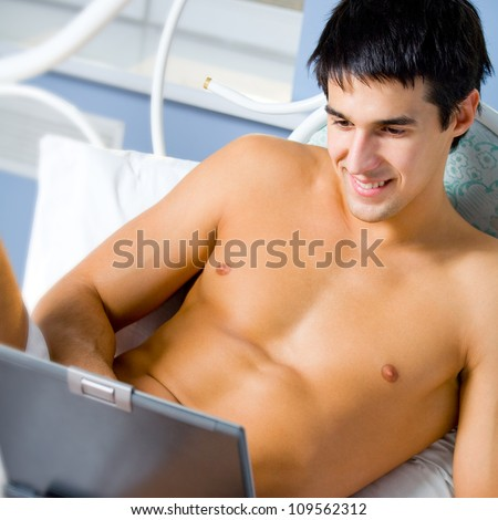 Cheerful young man working with laptop, at home - stock photo