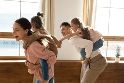Cheerful young married couple piggyback riding small daughters play together active games running in living room catching each other having fun in modern living room. Family playtime with kids concept