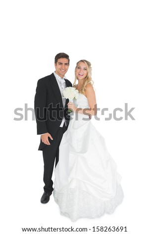 Cheerful young married couple posing smiling at camera on white background