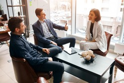 cheerful young men and beautifulwoman sittig on the armchairs having fun, showing thumb up, expressing good feeling and emotion in the office with modern interior and panorama window