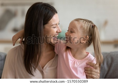 Photo of Cheerful young mom embracing adorable cute little daughter laughing having fun playing at home, happy small kid hugging adult funny mum bonding sit on sofa enjoying single parent and child lifestyle