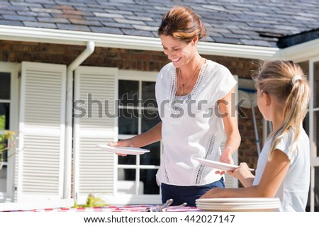Cheerful young mother arranging plates on dining table outside house. Daughter helping mother arrange the table in the courtyard. Daughter giving plates to mother.