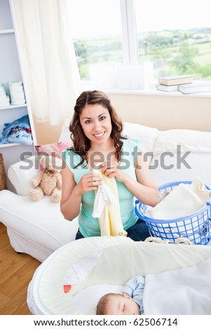 Cheerful young mother doing the laundry while her baby is sleeping in the living-room at home