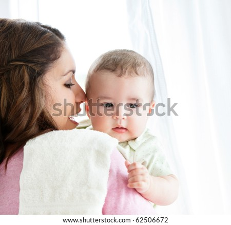 Cheerful young mother taking care of her adorable baby at home