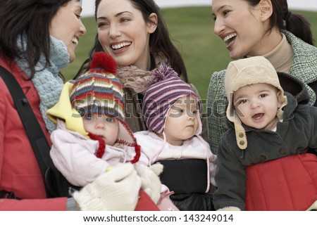 Cheerful young mothers with babies in slings chatting outdoors
