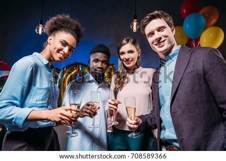 cheerful young multiethnic friends holding glasses of champagne and smiling at camera #708589366